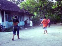 Bermain bola di pekarangan.