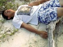 Tiduran di tepi pantai.